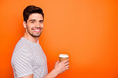 Profile photo of funny attractive cheerful guy hold hand hot takeout coffee beverage friendly toothy smiling wear striped t-shirt isolated bright orange color background