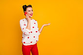 Photo of pretty lady hold telephone hand talking best friend telling romantic date story inspired wear hearts pattern white pullover red trousers isolated yellow color background