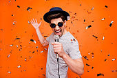 Photo of attractive crazy funky youngster guy singing karaoke using microphone confetti falling wear retro hat sun specs striped t-shirt isolated bright orange color background