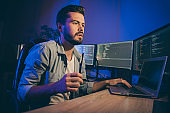 Profile photo of it specialist guy working late at night sitting office chair looking monitors website debugging expert have problems service error dark office indoors
