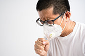 middle aged Asian man coughing in medical mask or N95 dust protective