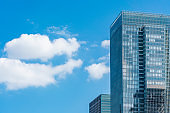Looking up view of panoramic modern city skyline with blue sky and cloud in  Tokyo, Japan