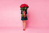 Full length photo of charming chic lady hold arms large roses bouquet hiding face shy person wear short green dress red high-heels isolated pastel pink color background