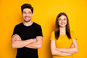 Photo of cheerful cute pretty sweet nice couple of two people standing confidently optimisticly with arms crossed isolated over vivid color background wearing black t-shirt