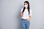 Portrait of serious worried girl use smartphone search epidemic covid-19 information follow share repost news wear t-shirt denim jeans medical mask isolated over gray color background