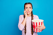 Portrait of scared youngster girl watch horror series hold box with pop corn feel fear bite nails wear good looking clothes isolated over bright color background