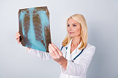 Photo of experienced retired pensioner woman oncologist hold x-ray photo analyze covid-19 patient lungs diagnosis bronchitis asthma have stethoscope isolated over gray color background