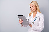 Portrait of focused retired pensioner woman doc use tablet search corona virus medication pneumonia treatment wear white coat isolated over gray color background