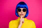 Closeup photo of attractive lady modern look hold finger on lips wear retro specs stylish yellow turtleneck blue short blue wig isolated vibrant pink color background