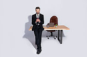Full length photo of handsome business guy hold telephone communicating colleagues partners wear black blazer shirt pants shoes suit lean table isolated grey background