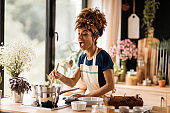 Beautiful African American woman having fun in her kitchen