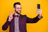Photo of handsome elegant clothes attractive guy business man hold telephone making selfies showing v-sign symbol good mood wear specs tie bow shirt blazer isolated yellow color background