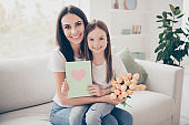 Photo of pretty little girl young charming mommy sitting cozy sofa holding hands 8 march present postcard tulips flowers from daddy affection emotions casual clothing home indoors