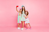 Full body photo of cute three people with long brunette blonde hair making selfie wearing skirt dress headbands isolated over pink background