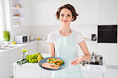 Have your gastronomy masterpiece, Photo of housewife lady chef showing grilled salmon trout fillet steak roasted garnish cook dinner one person portion wear apron modern kitchen indoors