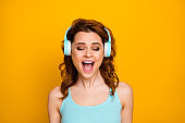 Photo of pretty funny lady listen modern technology headphones songs good mood singing loudly rejoicing wear casual teal tank-top isolated vivid yellow color background