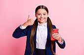 Portrait of her she nice attractive cheerful cheery confident small little girl using device app showing thumbup advice recomment isolated over pink pastel color background