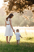 mother and son walking in the park on summer sunny day. mother's, baby's day. family concept