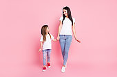 Full length body size view of two nice attractive lovely pretty cheerful cheery careful friendly best sisters walking enjoying holding hands isolated over pink pastel color background