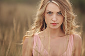 close up portrait of beautiful young blond woman outdoors in field. copy space