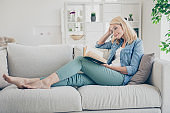 Profile photo of attractive aged mature homey lady sitting comfy sofa couch barefoot reading interesting historic novel book stay home quarantine time weekend living room indoors