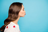 Close-up profile side view portrait of her she nice attractive lovely lovable pretty cute sweet tender girl wearing white pullover kissing isolated on bright vivid shine vibrant blue color background