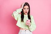 Photo of charming shocked lady hold telephone arm on head read awful news unfollowers blog statistics wear casual green crop pullover jeans skirt isolated pink pastel color background