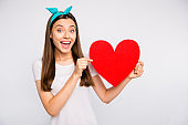 Portrait of amazed excited girl hold red big paper card heart gift for 14-february celebration with her boyfriend scream wow omg wear lifestyle outfit isolated over white color background