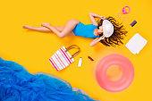 Full size high angle above flat lay view photo of beautiful lady lying seaside resort sunbathing panama on head surrounded beach stuff wear bodysuit isolated yellow color background