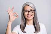 Photo portrait of happy senior woman with grey hair wearing glasses showing okay sign smiling isolated on grey color background
