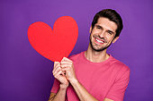 Portrait of cheerful candid guy hold big red paper card heart he get on 14-february celebration feel grateful wear style stylish trendy clothes isolated over bright color background