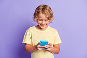 Photo of positive little boy chatting on cellphone wear yellow t-shirt isolated over violet color background
