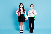 Full length photo of two girl boy schoolchildren friends hold hands wear respiratory uniform backpacks isolated blue color background