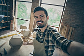 Close up photo of successful professional workman feel positive make selfie hold hand show his renew hardwood wooden shelf production in home house garage