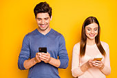 Portrait of positive two people romantic couple use smartphone read social network news wear blue pink sweater isolated over bright color background