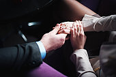Young couple holding hands. Wedding day. Indoors