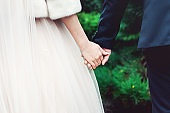 Young couple holding hands. Wedding day. Outdoors