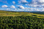 Aerial drone shot of several clean energy wind turbines in a rural area of South Wales, UK