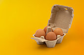 open egg box brown on yellow background