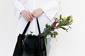 Beautiful young woman wearing white shirt, blue jeans and black shoes holding a bag and flowers on white background