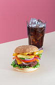 Fresh juicy beef hamburger with french fries placed on pink creative trendy background