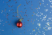 Sparkles with red bauble on blue trendy background. Festive backdrop for projects. Flat lay style. Top view. Color of the year.