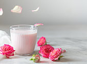 Moon milk prepares with pink rose flower with flying petals. Trendy relaxing bedtime drink form Ayurvedic traditions