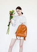 Beautiful young woman with nude color make-up wearing white and blue striped dress shirt and white skirt and brown backpack holding bouquet of flowers on white background