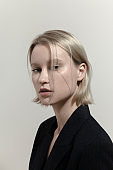 Young blond woman with short straight hair in black suit Dramatic lighting Portrait