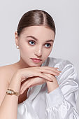 Beautiful young woman wearing luxury gold watches Designer clothes white silk blouse Elegant beauty Fashion model portrait