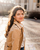 Beautiful young woman at city street. Happy tourist girl walking outdoors. Spring portrait of pretty brunette female posing in old town. Follow me to city