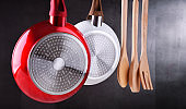 Two hanging frying pans and kitchen utensils