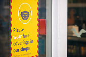 Face coverings warning sign displayed outside a shop in Southwold, UK