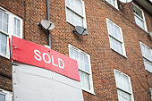 Sold sign with council housing flats in the background in London